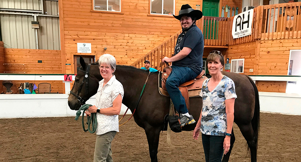 Two volunteers walking horse patient is riding during a session